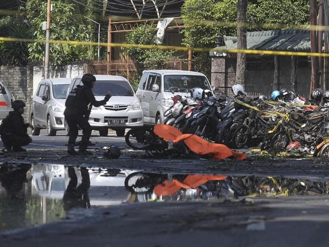 Members of police bomb squad inspect wreckage of motorcycles at the    site where an explosion went off outside a church in Surabaya, East Java, Indonesia. Picture: AP Photo/Trisnadi