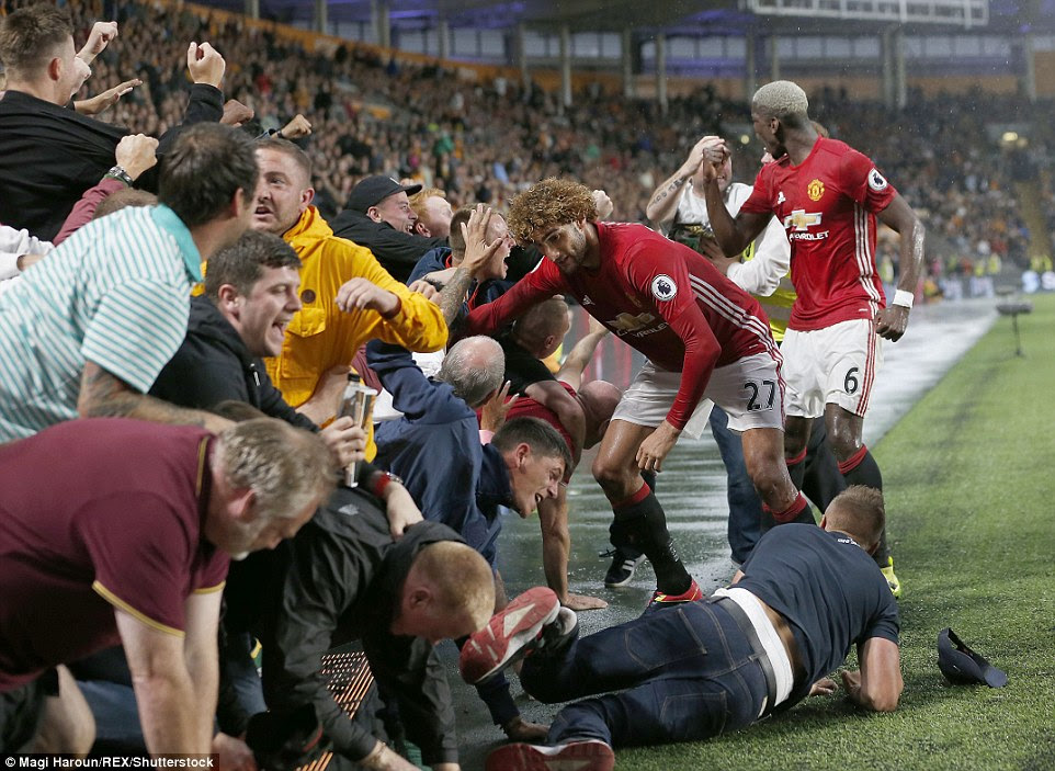 Fellaini reached into the crowd to help as United's fans celebrated their dramatic late winner