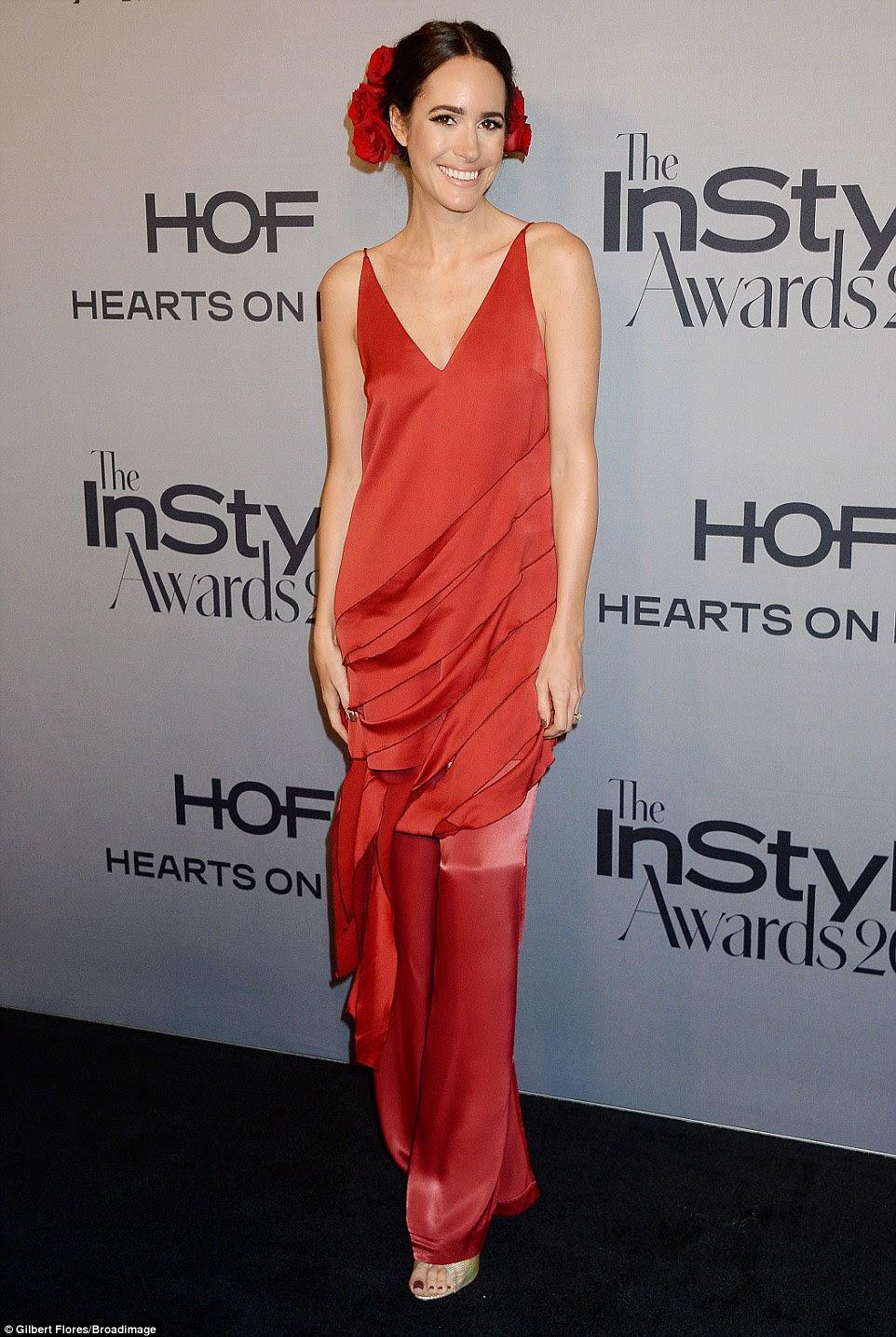 Alerta vermelho: Louise Roe usava flores em seu cabelo que combinavam com seu vestido maxi vermelho