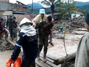 Rescue workers try to help those caught up in the mudslide in Colombia. Pic: Colombian Military Forces