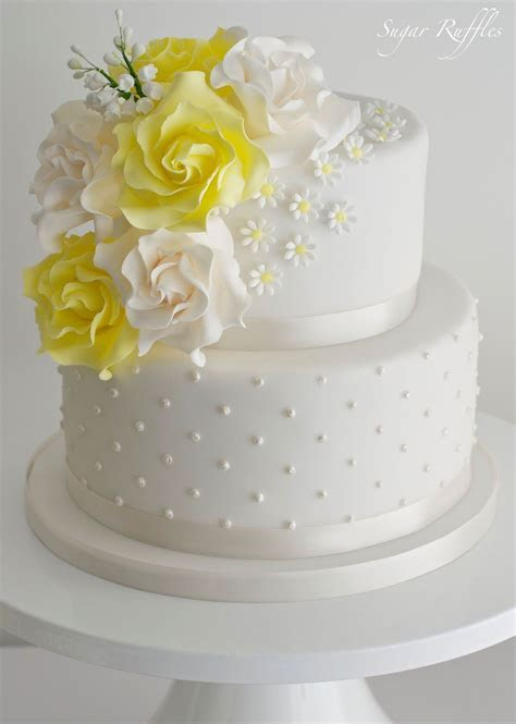 A 2 tier wedding cake with swiss dots, topped with a