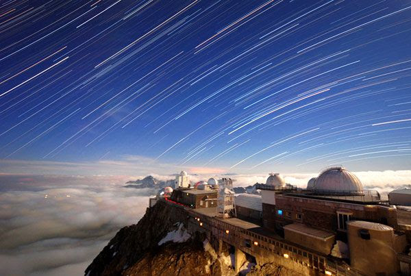 A time-lapse shot showing stars moving across the sky above the Pic du Midi Observatory.