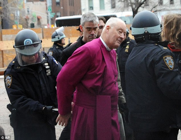 Cuffed: Police arrest retired Episcopal Bishop George Packard during an Occupy Wall Street demonstration in New York City. He was among those arrested when protesters broke a chain link fence to access a vacant lot