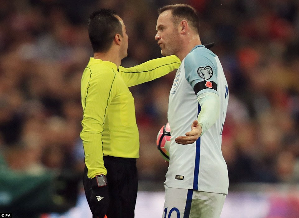 An agnry Rooney remonstrates with the linesman as a decision goes against England during a feisty encounter