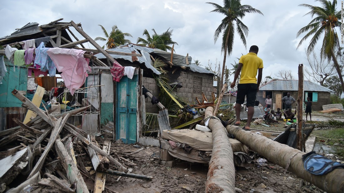 A young man walks on a palm tree in front of a destroyed house in Croix Marche-a-Terre, in south-west Haiti.