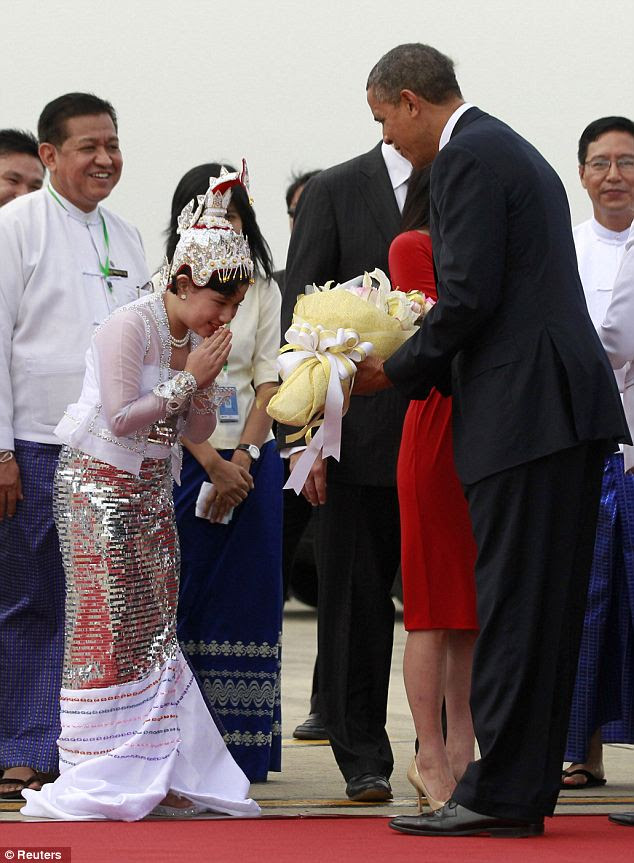 Embracing: A young girl in traditional dress hands the President a bouquet at his arrival