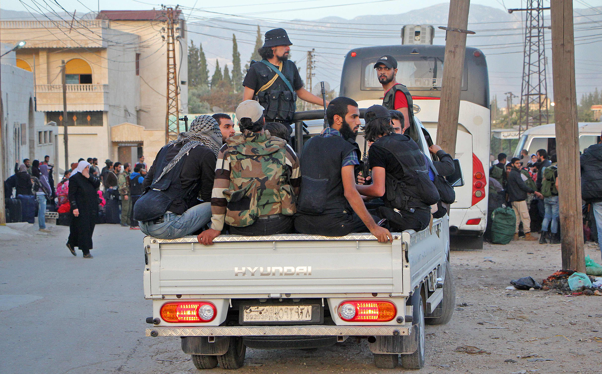 Rebel fighters arrive in Idlib following their evacuation from Qudssaya and al-Hamah, neighbourhoods of the Syrian capital, on October 14, 2016. / AFP PHOTO/AFP/Getty Images