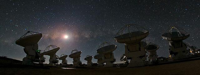 The ALMA radio telescopes under a starry sky