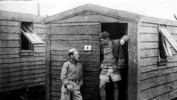 A historical photo believed to have been taken of prisoners in front of 'public works huts' that housed them, at the ...