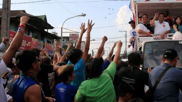 Rodrigo Duterte (top right), Philippines presidential candidate and a local mayor, raises his fist during a motorcade campaign at Cainta Rizal, east of Manila (12 April 2016)