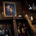 A bartender placed a candle near a portrait of John F. Kennedy and Jacqueline Kennedy in the Kennedy Room bar in Dallas.