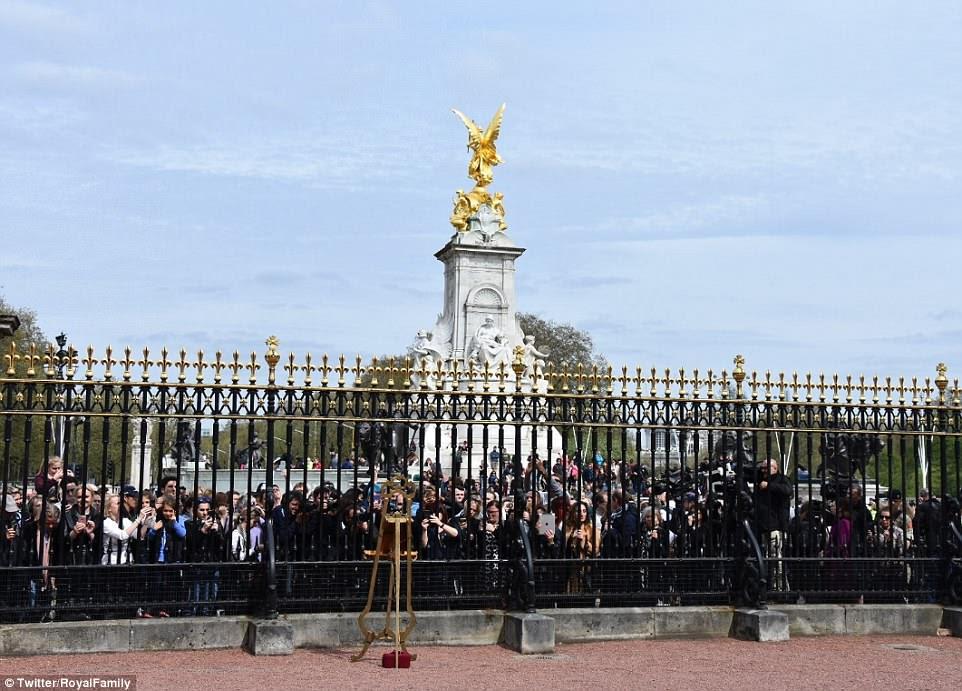 Los fanáticos reales en el Palacio de Buckingham se reúnen para echar un vistazo al caballete anunciando el nacimiento del bebé real hoy