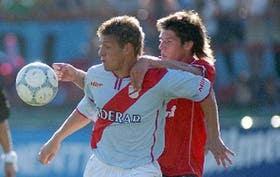 Germán Denis, el autor del primer tanto de Arsenal, intenta dominar el balón y aguanta la marca del defensor Carlos Mateu