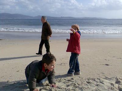 Iago y Diego en la playa con el abuelo Toño al fondo
