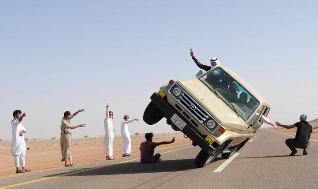 Carro é visto trafegando com passageiros em apenas duas das quatro rodas (Foto: Mohamed Al Hwait/Reuters)