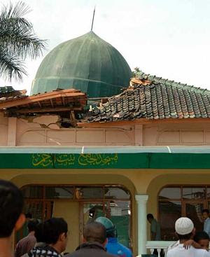 Residents gather outside a mosque damaged by a powerful earthquake at Cisaat village, West Java September 2, 2009.