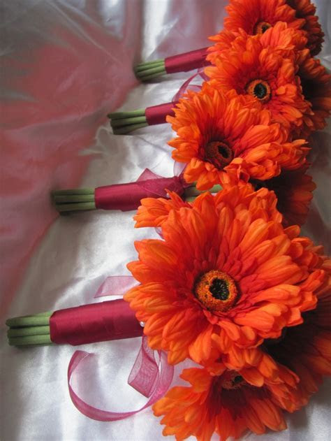 #orange gerbera bridesmaid bouquets with burgundy ribbon