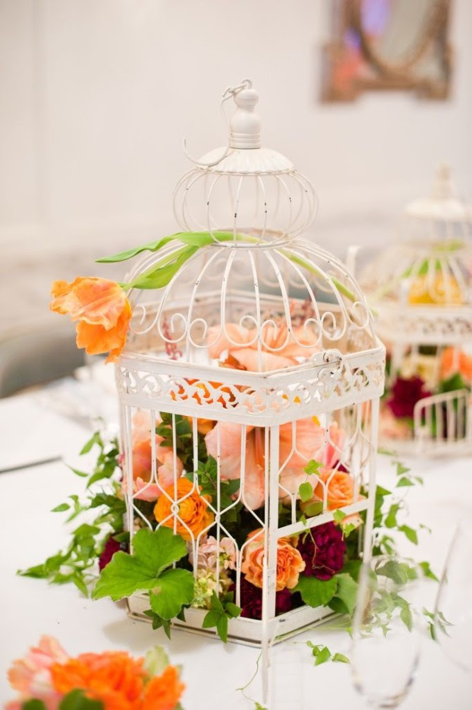 ein weißer Käfig mit üppigen orange, peachy und Burgund Blüten für eine mutige, Hochzeit