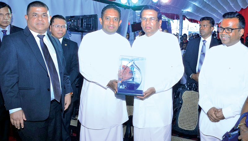 President Maithripala Sirisena receiving the token of appreciation from Minister Chandima Weerakkody. Skills Development and Vocational Training Deputy Minister Karunaratne Paranavithana looks on. Picture by Sudath Malaweera.