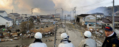 Firefighters and others watch smoke from burning buildings in Kesennuma, Miyagi Prefecture, Saturday morning, March 12, 2011 after Japan's biggest recorded earthquake slammed into its eastern coast Friday. (AP Photo/Kyodo News)