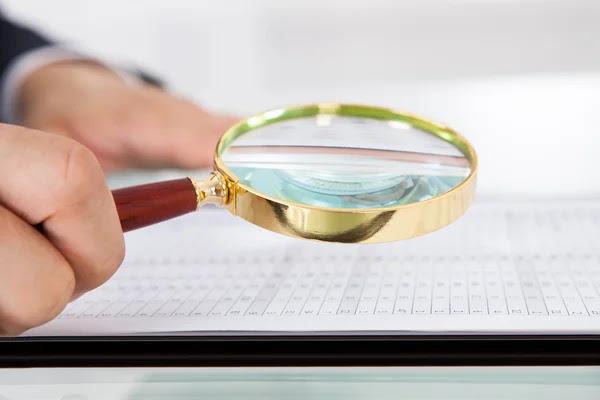 Empresario examinando con lupa en la oficina de auditoría — Foto de Stock #46203357