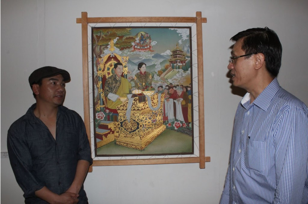 """Rinchen Wangdi (at left) beside his painting """"King"""""""