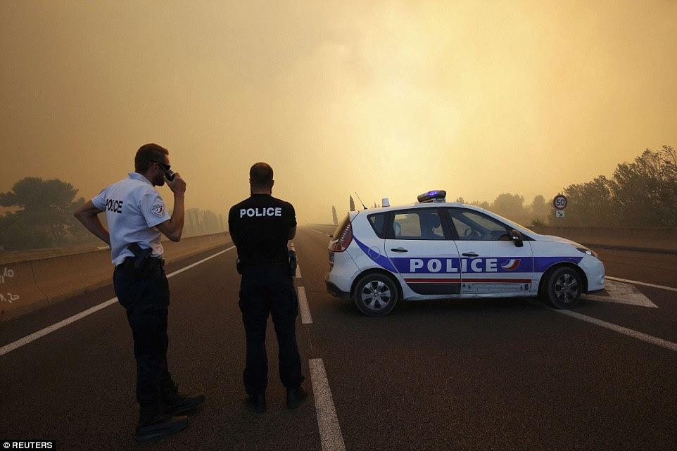 A polícia francesa diante de um obstáculo como o fumo enche o céu e bloqueia o sol como fogos queimam norte de Marselha