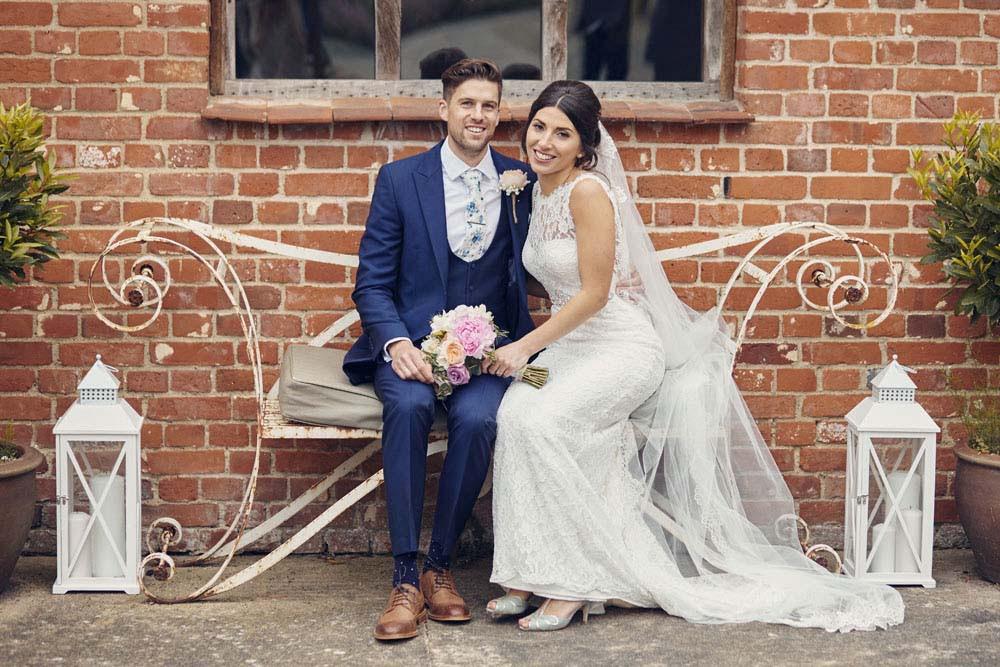 Bride & groom on bench at Moreves Barn in Sudbury Suffolk - www.helloromance.co.uk