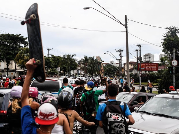 Fã levanta o skate ao acompanhar a passagem do carro com o caixão (Foto: Luiz Fernando Menezes / Fotoarena / Estadão Conteúdo)