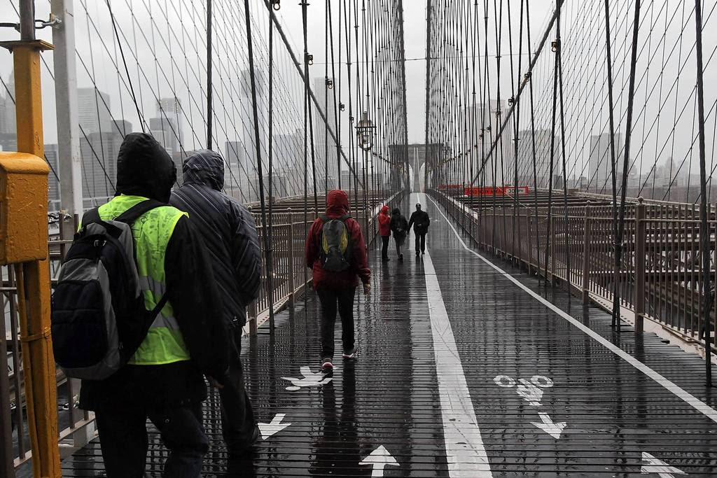 People walk across the Brooklyn Bridge as Hurricane Sandy begins to affect New York City. The storm, which threatens 50 million people in the eastern third of the U.S., is expected to bring days of rain, high winds and possibly heavy snow. New York Governor Andrew Cuomo announced the closure of all New York City will bus, subway and commuter rail service as of Sunday evening.