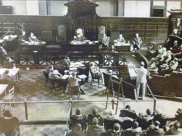 "Trial of Jack ""Legs"" Diamond in Rensselaer County Courthouse, Troy, on Dec. 16, 1931. Diamond is seated at the center table left of the white-haired attorney, co-counsel Abbott Jones.To Diamond's left is chief defense attorney  Daniel H. Prior of Albany. The witness testifying is Grover Parks of Greene County, who is being questioned by Assistant Attorney Gerneral John T. Cahill. Justice F. Walter Bliss of Middleburgh, Schoharie County, presides. Diamond's wife, Alice, is seated in the front row, far left.  (Photo courtesy the Jones law firm)"