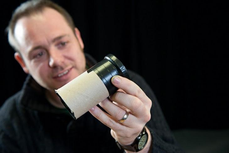 Hombre que tiene un lente fotográfico en su mano con un rollo de papel higiénico