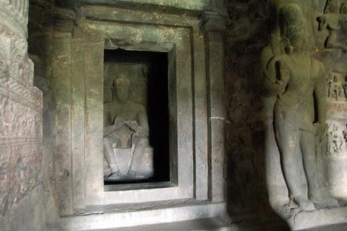 Ein Buddha in einem Schrein, beschützt durch ein Yaksha.