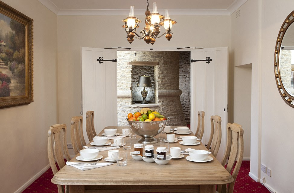 A chandelier hangs over the fruit bowl on the rustic wooden table in the breakfast room of Bath Lodge Castle