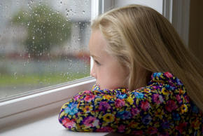 Girl looking out window on rainy day