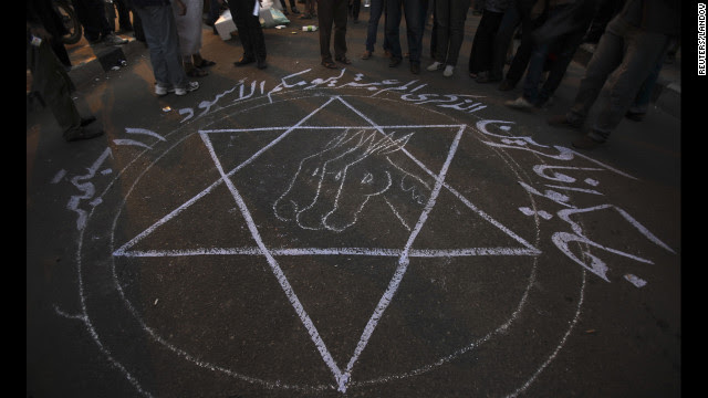 """People stand around a drawing that says """"Remember your black day 11 September"""" during the protest in Cairo."""