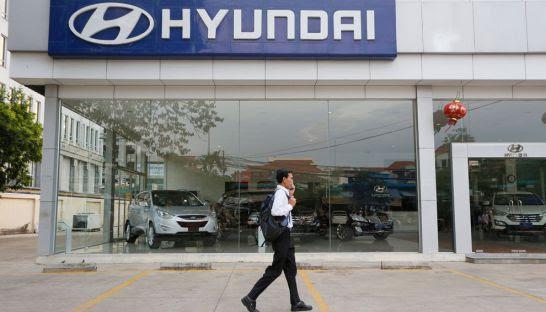 A man walks past a Hyundai dealership showroom in Phnom Penh