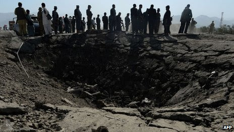 Afghan policemen and villagers look on near a crater at the scene of suicide attack in Maidan Shar, the capital city of Wardak province