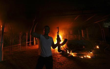 A protester reacts as the U.S. Consulate in Benghazi is seen in flames during a protest by an armed group said to have been protesting a film being produced in the United States September 11, 2012. An American staff member of the U.S. consulate in the eastern Libyan city of Benghazi has died following fierce clashes at the compound, Libyan security sources said on Wednesday. Armed gunmen attacked the compound on Tuesday evening, clashing with Libyan security forces before the latter withdrew as they came under heavy fire. REUTERS-Esam Al-Fetori (