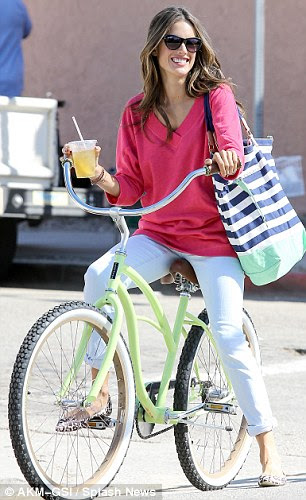 Hot wheels: Alessandra donned pink and white as she hopped on a bike and sipped a drink