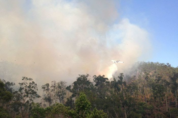A firefighting aircraft drops water onto a bushfire at Nankin, near Rockhampton.