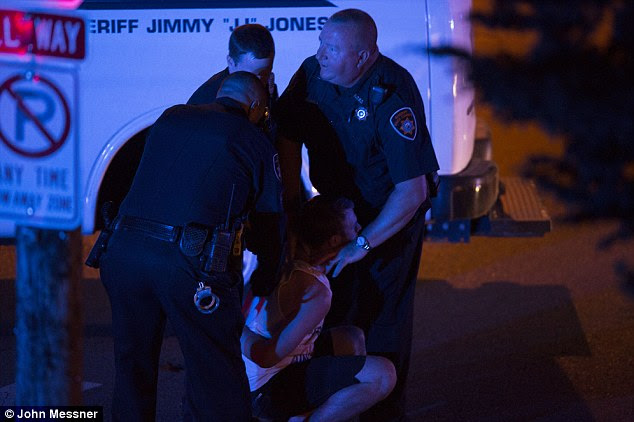 Incapacitated: The young man sinks to the ground with his hands cuffed behind his back