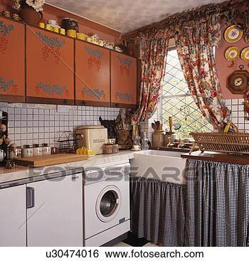 Stock Images of Checked curtains below sink in small kitchen with ...