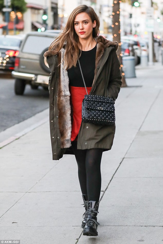 Empacotada: A atriz de 35 anos, vestida com uma jaqueta verde-oliva e uma saia vermelha brilhante que combinava com calças pretas e botas de combate