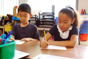 students write on worksheets in classroom
