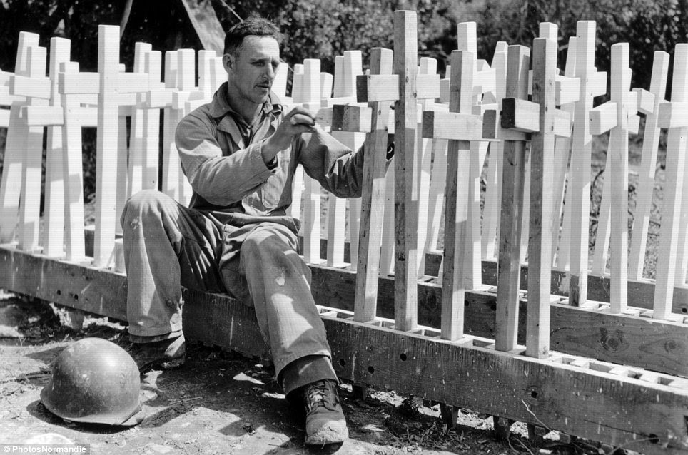 Hard at work: Private Alfonton Ortega, from Los Angeles, sets up wooden crosses which will be used as grave markers