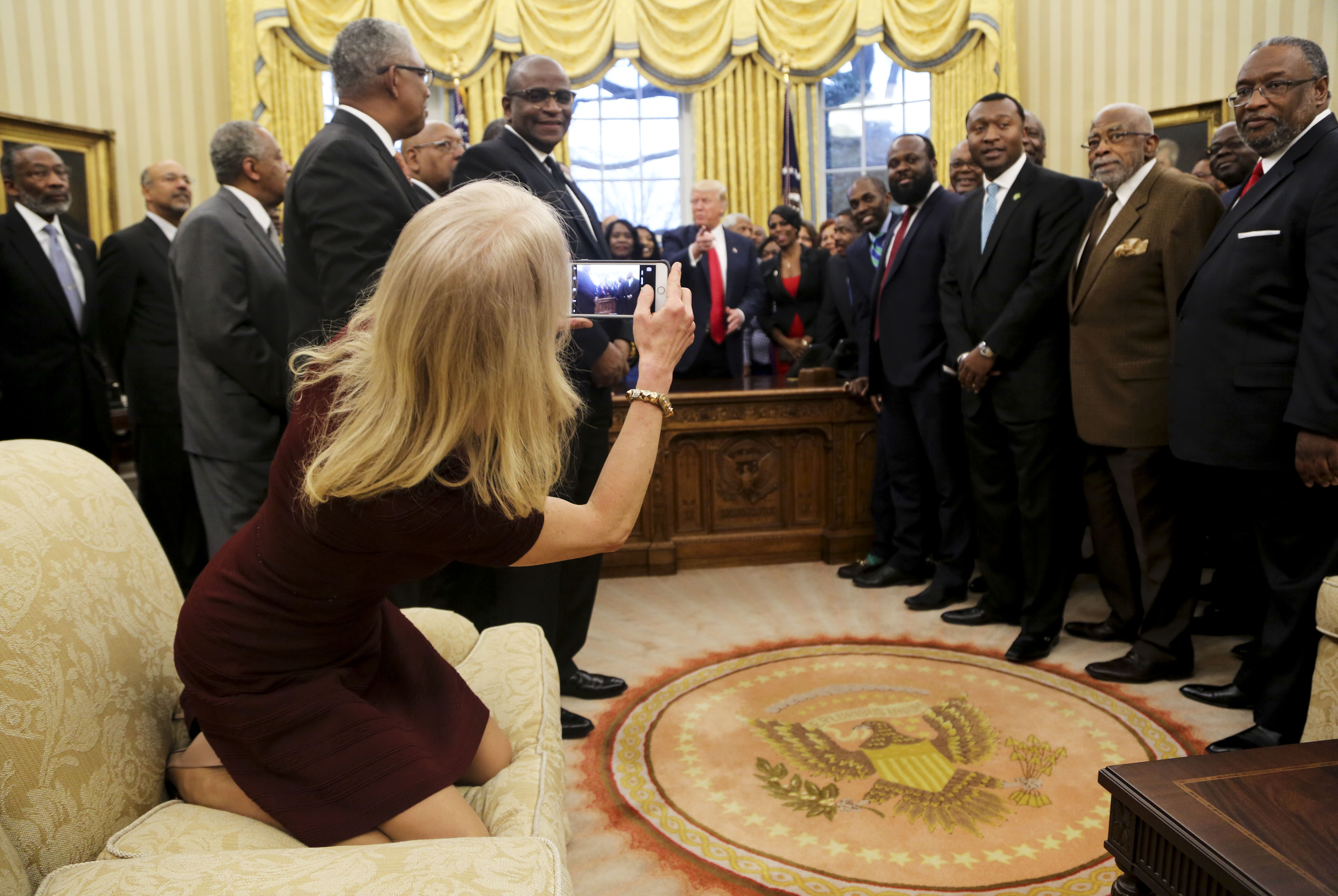 WASHINGTON, DC - FEBRUARY 27: Counselor to the President Kellyanne Conway takes a picture of U.S. President Donald Trump with members of the Historically Black Colleges and Universities in the Oval Office of the White House, on February 27, 2017 in Washington, DC. (Photo by Aude Guerrucci-Pool/Getty Images)