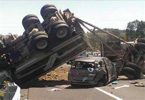 '图2:二零一三年十二月三日车祸现场航拍视频截图图,大货车断成两截翻倒在地,被压在前半部下面的就是金和家人乘坐的轿车。'