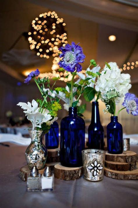 Cobalt blue bottles, silver mercury glass, and wood rounds