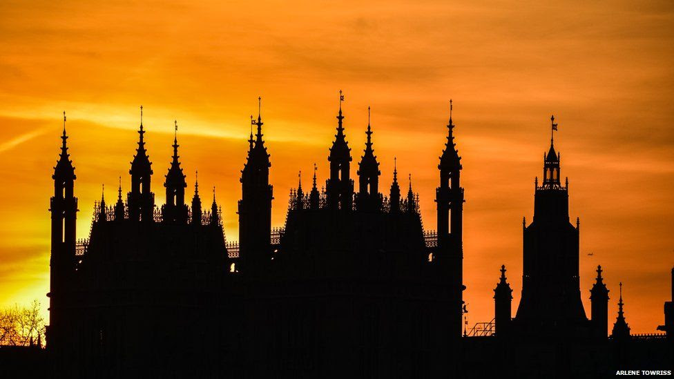 A cathedral's spires are silhouetted against a yellow sunset